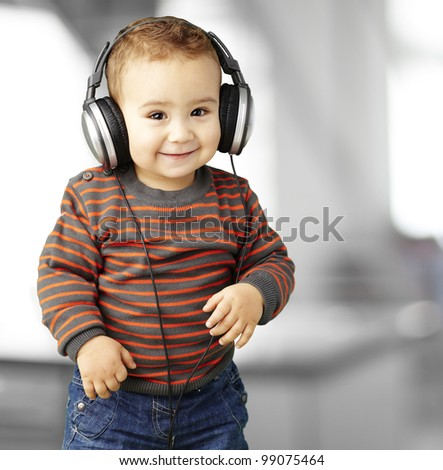 portrait of a handsome kid listening to music and smiling indoor - stock photo