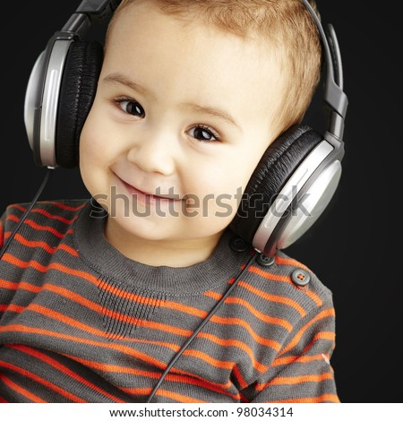 portrait of a handsome kid listening to music and smiling over b - stock photo