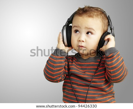portrait of a handsome kid listening to music looking up over grey background - stock photo