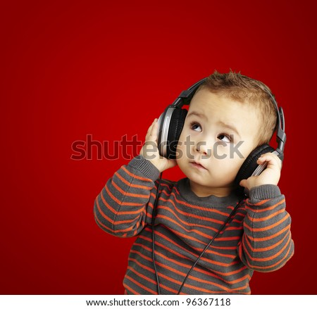 portrait of a handsome kid listening to music looking up over re - stock photo