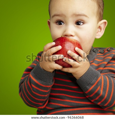portrait of a handsome kid sucking a red apple over green backgr - stock photo