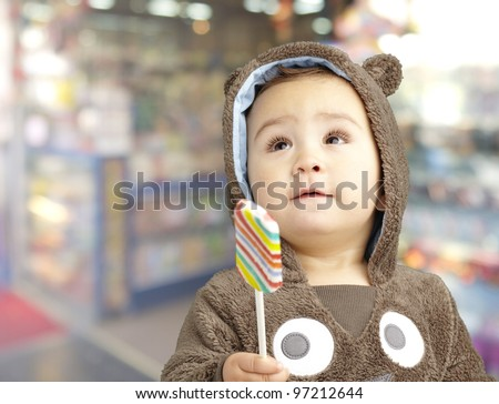portrait of a handsome kid wearing a brown bear sweatshirt holding candy against a candy shop background - stock photo