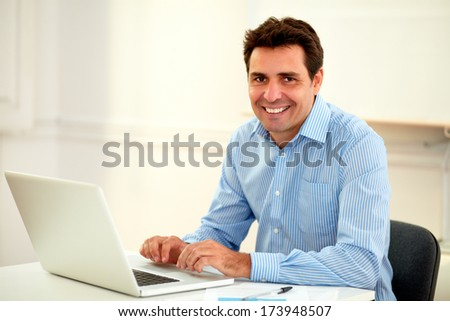 Portrait of a handsome latin businessman smiling at you while working on his laptop and sitting on office desk - copyspace