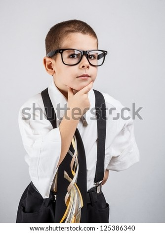 Portrait of a handsome little boy in a business suit thinking - stock photo