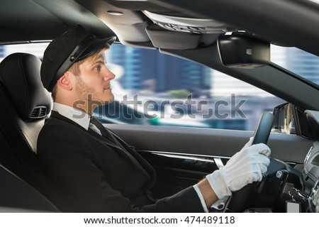 Portrait Of A Handsome Male Chauffeur Driving A Car