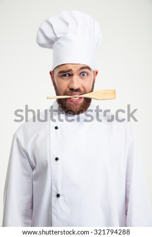 Portrait of a handsome male chef cook holding spoon in teeth isolated on a white background - stock photo