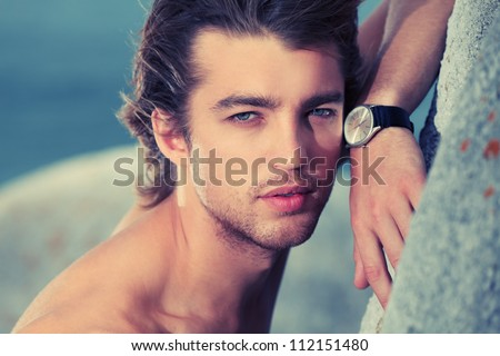Portrait of a handsome male model posing at the seaside. - stock photo