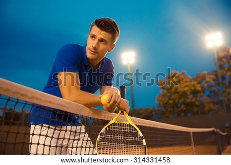 Portrait of a handsome male tennis player standing in the court and looking away - stock photo