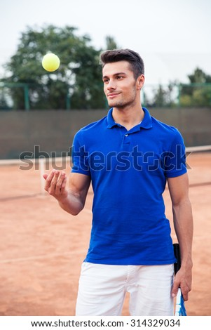 Portrait of a handsome male tennis player standing outdoors - stock photo