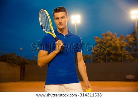 Portrait of a handsome male tennis player standing with racket outdoors and looking at camera - stock photo