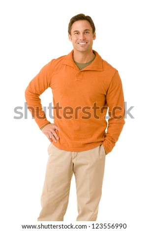 portrait of a handsome man casual dressed wearing khaki pants and an orange sweater smiling isolated on a white background - stock photo