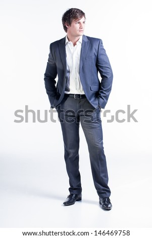 portrait of a handsome man dressed in a gray suit with his hand in his pocket looking to the side - stock photo