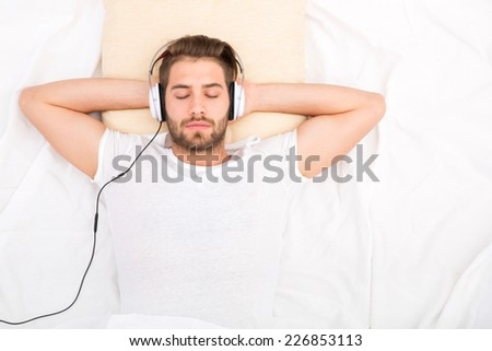 Portrait of a handsome man from above with headphones in bed.