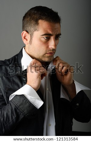 Portrait of a handsome man getting dressed - stock photo