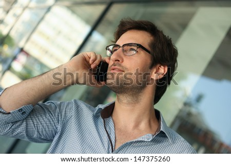 Portrait of a handsome man having phone conversation - stock photo