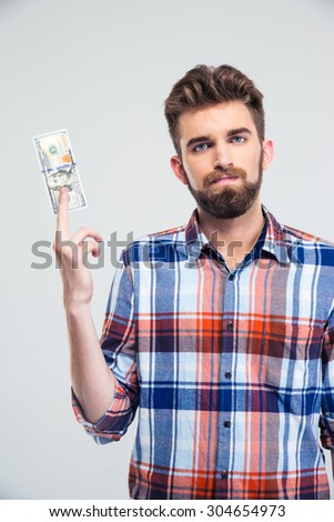 Portrait of a handsome man holding bill of USA dollar isolated on a white background and looking at camera