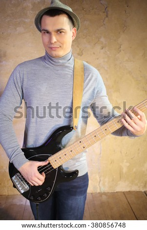 Portrait of a handsome man in a hat with a guitar in his hands - stock photo