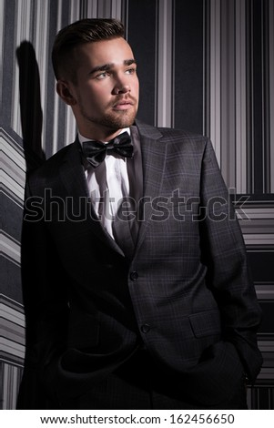 Portrait of a handsome man in a suit and a tie who is posing over a striped background - stock photo