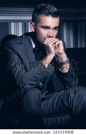 Portrait of a handsome man in a suit who sits in the spotlight over a striped background - stock photo