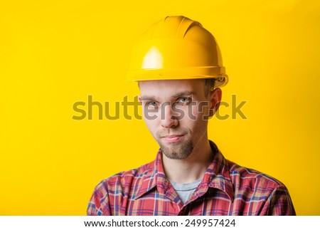Portrait of a handsome man in a yellow construction helmet