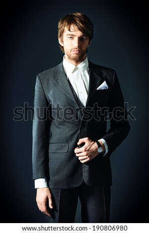 Portrait of a handsome man in elegant black suit and spectacles. Over dark background.