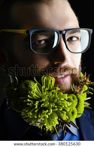 Portrait of a handsome man in spectacles and with a beard of green flowers. Men's beauty. Barbershop. - stock photo