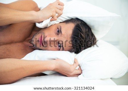 Portrait of a handsome man lying on the bed with pillow on head at home - stock photo