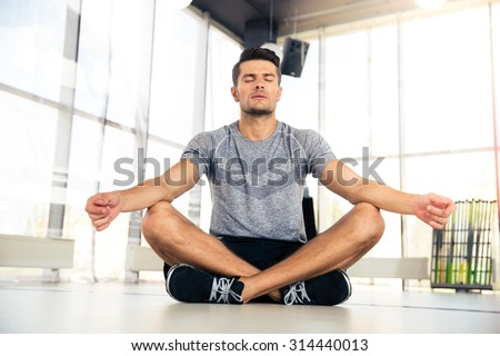 Portrait of a handsome man meditating in fitness gym