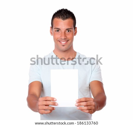 Portrait of a handsome man on stylish t-shirt holding a blank card while is looking at you on isolated background - copyspace