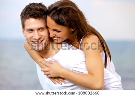 Portrait of a handsome man piggybacking his girlfriend on a vacation - stock photo