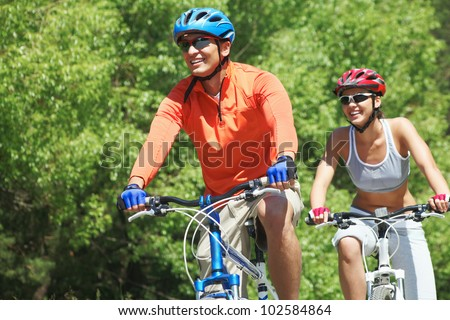 Portrait of a handsome man riding a bike with his wife on background