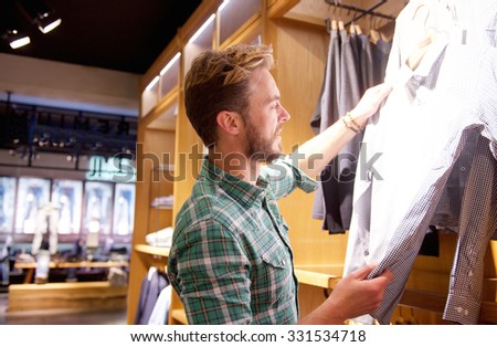 Portrait of a handsome man shopping for clothes at store