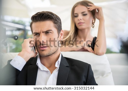 Portrait of a handsome man talking on the phone outdoors in restaurant with woman on background - stock photo