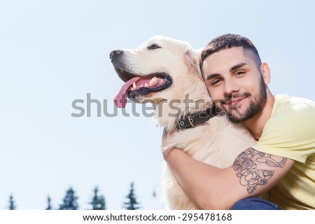 Portrait of a handsome man wearing yellow t-short and jeans with tattoo on his arm sitting on the grass, looking at us smiling and hugging his lovely golden retriever in the park - stock photo
