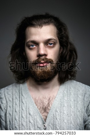 Portrait of a handsome man with a beard, long hair and big blue eyes