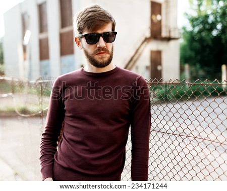 Portrait of a handsome man with a beard wearing glasses on a sunny day - stock photo