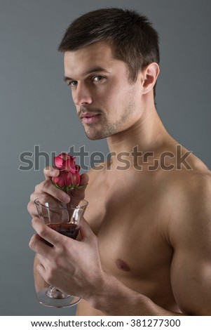 Portrait of a handsome man with a rose and a glass of wine.
