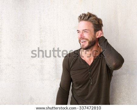 Portrait of a handsome man with beard laughing with hand in hair - stock photo