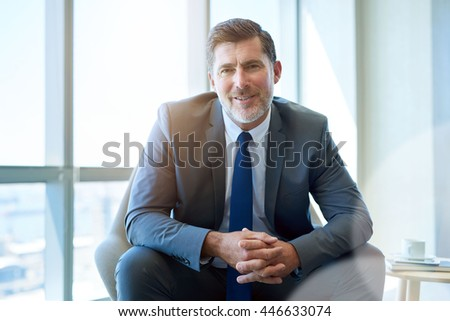 Portrait of a handsome mature business CEO smiling warmly at the camera while sitting in a modern office space with large windows and gentle sunflare - stock photo