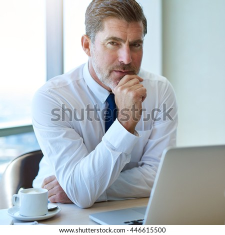 Portrait of a handsome mature business leader with greying hair and attractive short beard, sitting at this desk with a laptop and looking at the camera with an intense and confident expression - stock photo