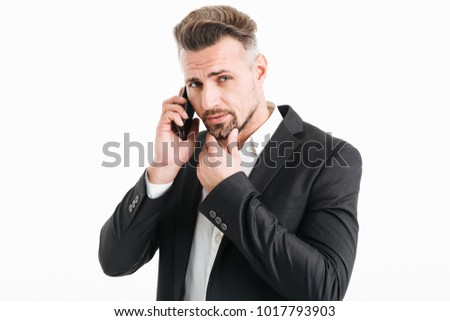 Portrait of a handsome mature businessman dressed in suit talking on mobile phone isolated over white background