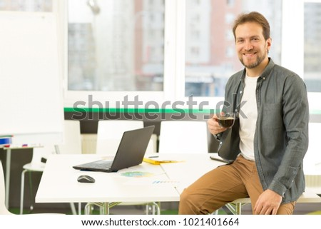 Portrait of a handsome mature cheerful bearded casual businessman smiling to the camera sitting relaxed on his desk at the office enjoying coffee copyspace entrepreneurship success.