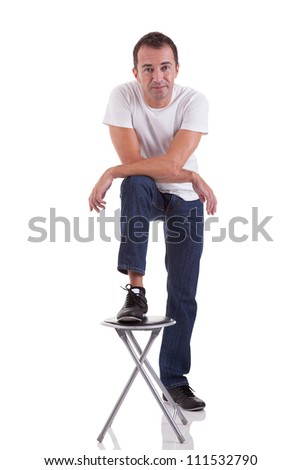 Portrait of a handsome middle-age man with his foot on a bench, on white background. Studio shot - stock photo