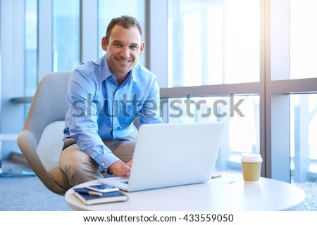 Portrait of a handsome middle-aged businessman sitting at a coffee table in a bright modern office space, typing on his laptop and giving the camera a warm and trustworthy smile - stock photo