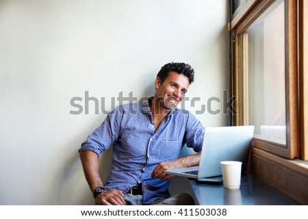 Portrait of a handsome modern man smiling with laptop at cafe - stock photo