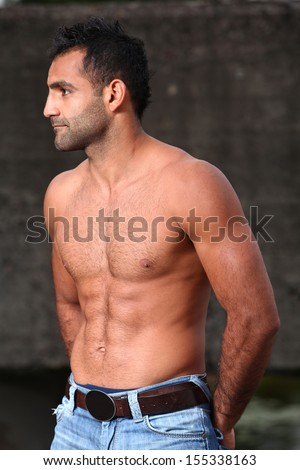 Portrait of a handsome, muscled man who is posing shirtless