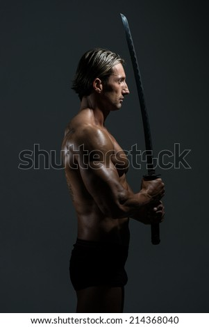 Portrait Of A Handsome Muscular Ancient Warrior With A Sword - stock photo