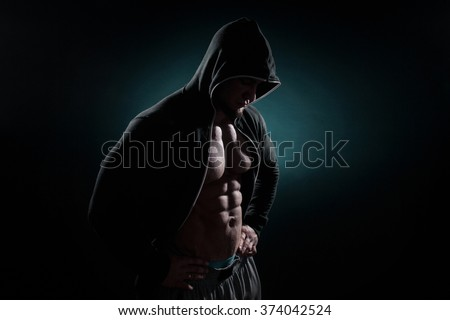 Portrait of a handsome muscular bodybuilder in hoodie posing over black background.  - stock photo