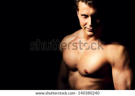Portrait of a handsome muscular bodybuilder posing over black background.