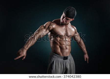 Portrait of a handsome muscular bodybuilder posing over black background - stock photo